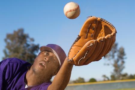 exerting: Baseball Outfielder Catching Fly Ball