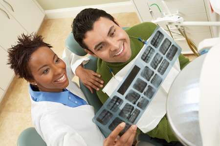 health facilities: Dentist and Patient Examining X-ray