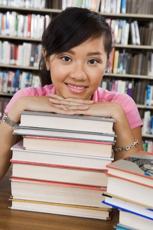 Student with a Stack of Books in Library Stock Photo - 5438269