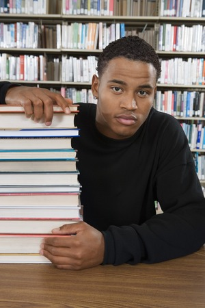 Student with a Stack of Books in the Library Stock Photo - 5438270