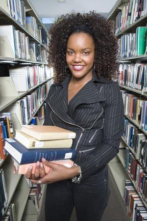図書館で本を保持している女子大学生の肖像画