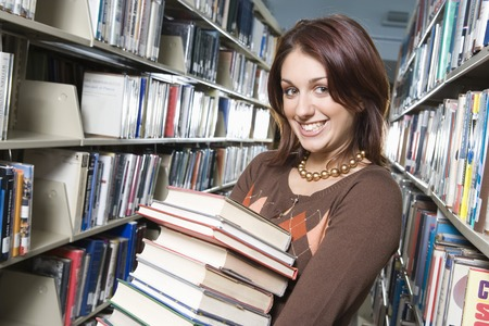 Female University student holding books in library, portrait Stock Photo - 5404510