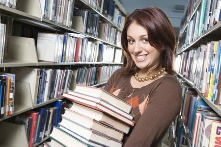 Female University student holding books in library, portrait Stock Photo - 5404510