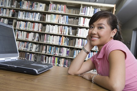 Female university student with laptop in library Stock Photo - 5438277