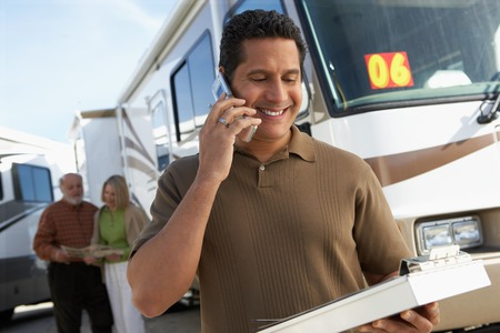 salespeople: Salesperson on Cell Phone while Couple Shops for an RV LANG_EVOIMAGES