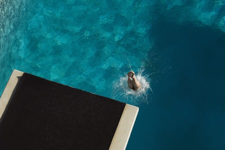 Young woman diving into swimming pool Stock Photo - 5404484