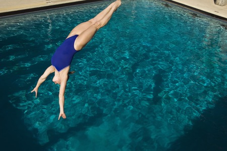 one piece swimsuit: Young woman diving into swimming pool