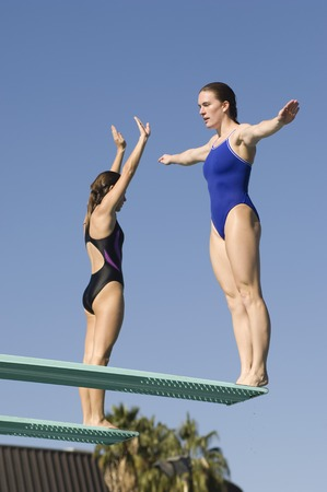 Two women standing on diving boards Stock Photo - 5404454