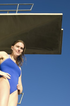 Female swimmer standing on diving board Stock Photo - 5404439