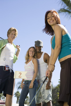 Young woman playing mini golf with friends Stock Photo - 5404313