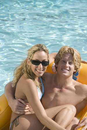 Portrait of young couple on inflatable raft in pool Stock Photo - 5404243
