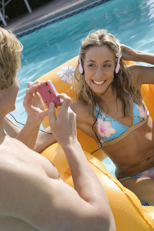Young man taking photograph on woman in inflatable raft Stock Photo - 5404242