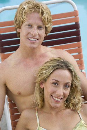Young couple on sunlounger by pool Stock Photo - 5404282