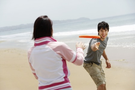 youthfulness: Couple Playing Frisbee on Beach