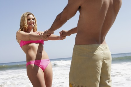 hands joined: Young Couple at the Beach LANG_EVOIMAGES