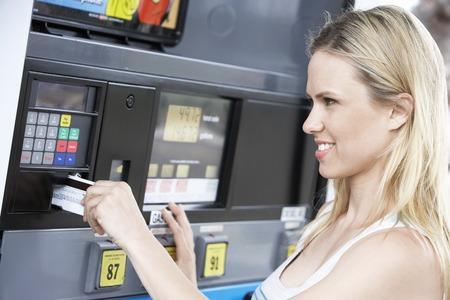 pagando: Mujer joven Llenando el tanque en la gasolinera
