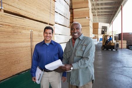 Manager et Ouvrier sur un quai de chargement de bois de construction Warehouse