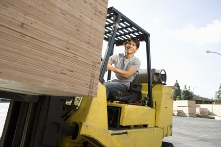 Mid-adult man driving forklift Stock Photo - 5438478