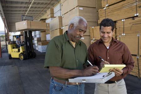 carretillas almacen: Los hombres de toma de stock en almac�n