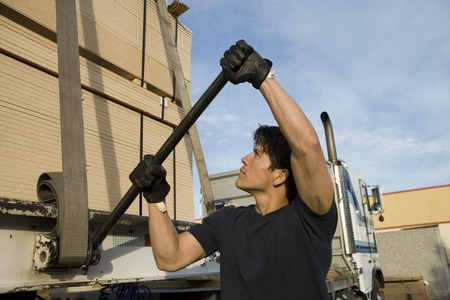 strapping: Mid-adult man adjusting strapping  of truck loaded with wood