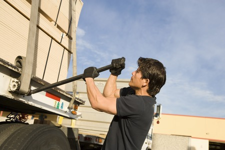 lever: Mid-adult man adjusting strapping of truck loaded with wood