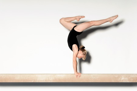 balance beam: Young Gymnast Doing Handstand en barra de equilibrio