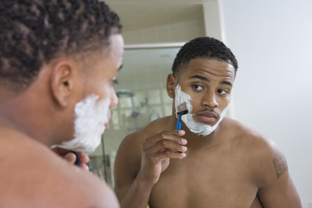 shaving cream: Portrait of young man shaving in bathroom LANG_EVOIMAGES