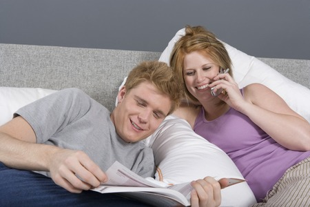 Young woman on phone in bedroom, man reading Stock Photo - 5449636
