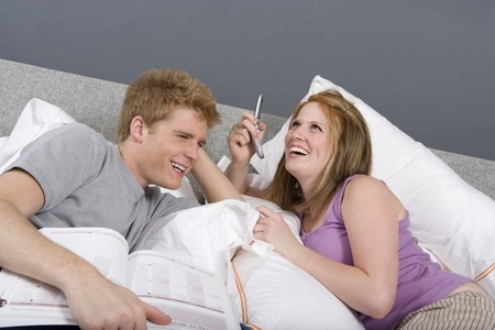 Young couple in bed, sharing mobile Stock Photo - 5449637
