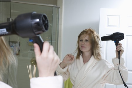 Young woman drying hair in front of bathroom mirror Stock Photo - 5449647