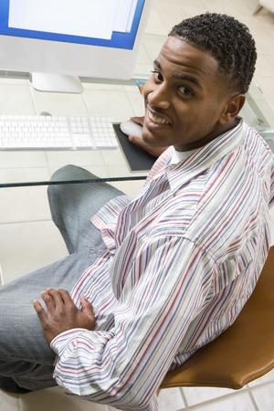 オフィスの PC に取り組んでいる若い男の肖像