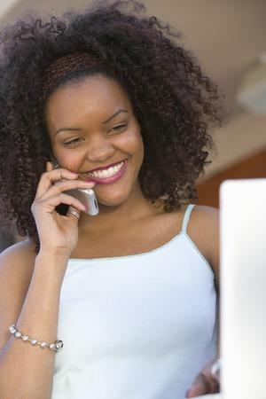 コンピューターの前に携帯で話している若い女性笑顔