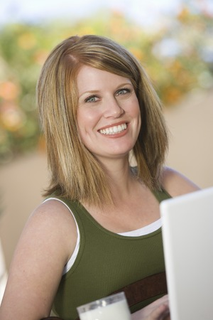 Portrait of young woman in front of computer, smiling Stock Photo - 5449697