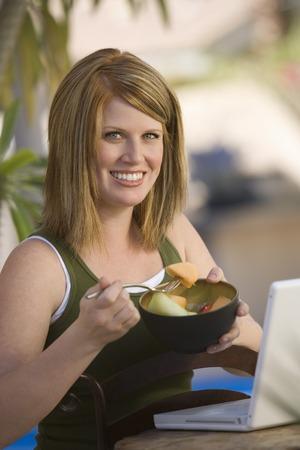 ラップトップ コンピューターの前にフルーツ サラダを食べる若い女性の肖像画