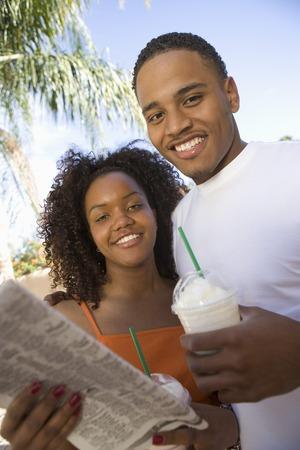 ミルクを保持している若いカップルを振る、屋外肖像画