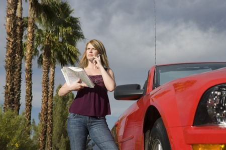 Young woman using mobile phone by convertible car Stock Photo - 5449741