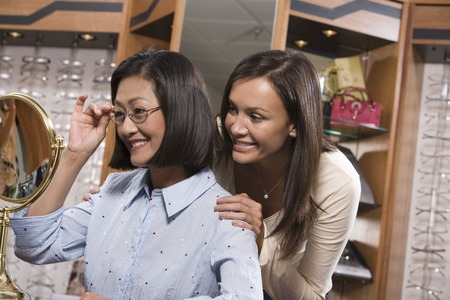 Two women trying on eyeglasses in store Stock Photo - 5449787