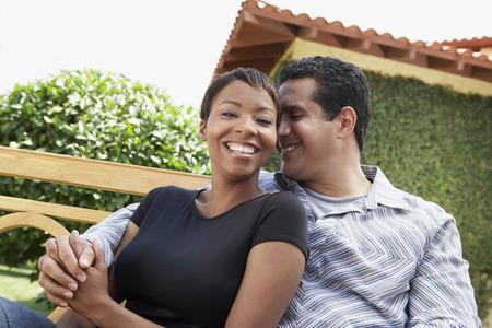 interracial marriage: Coppia seduta su una panchina in giardino