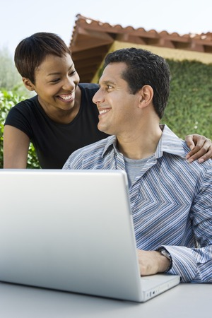 middle easterners: Couple using laptop in back yard