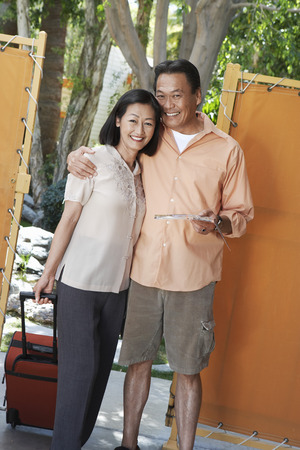 mature women only: Happy Couple with Luggage and Brochure