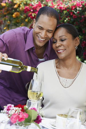 Man Pouring a Glass of Wine for His Wife Stock Photo - 5449960