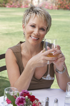 mature women only: Smiling Woman Enjoying a Glass of White Wine LANG_EVOIMAGES