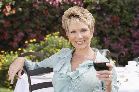 mature women only: Smiling Woman Enjoying a Glass of Red Wine