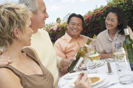 racially diverse: Friends Enjoying a Meal Outdoors LANG_EVOIMAGES