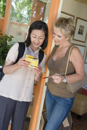 Two women reading guide book on vacation Stock Photo - 5449992