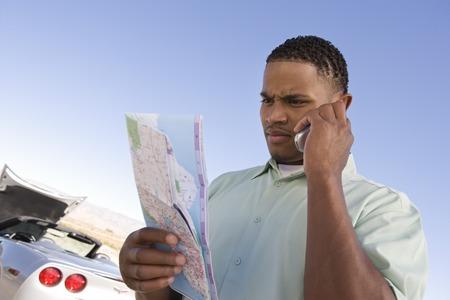 バック グラウンドで若い男の電話、壊れた車