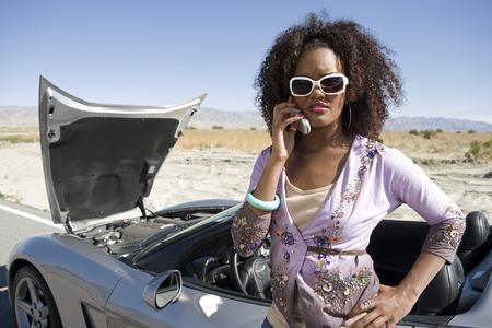 壊れた車のそばに立っている若い女性に電話をかける 写真素材