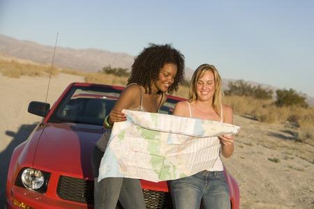 車の上に座って、地図を読んで二人の女性