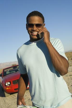 背景には、屋外で車の携帯電話で話している若い男 写真素材