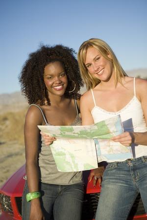 2 人の女性が車に座って、マップの読み取り 写真素材